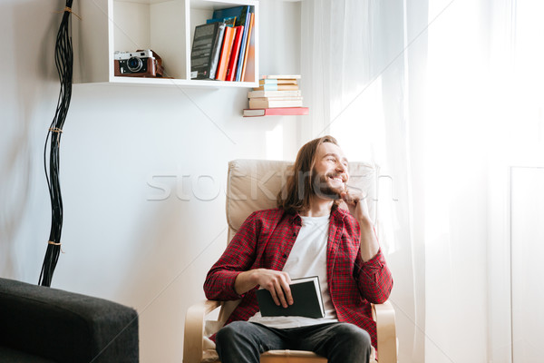 Happy young man with book sitting on armchair at home Stock photo © deandrobot