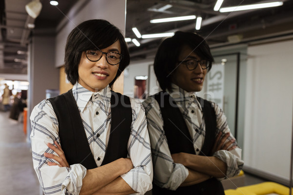 Cheerful young asian man wearing glasses standing with arms crossed Stock photo © deandrobot