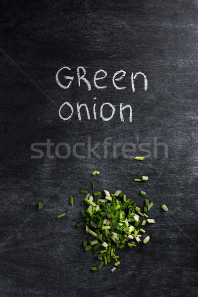 Cut green onion over dark chalkboard background. Stock photo © deandrobot