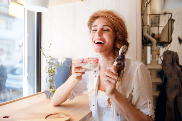 Smiling red haired woman sitting in cafe and eating dessert Stock photo © deandrobot