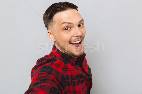 Happy man standing sideways and looking at camera Stock photo © deandrobot