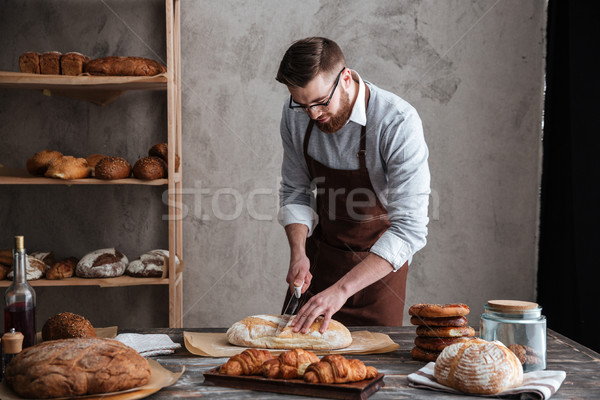 Concentrated young man baker cut the bread. Stock photo © deandrobot
