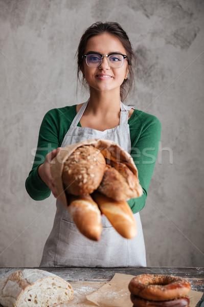 Függőleges kép női pék mutat táska Stock fotó © deandrobot