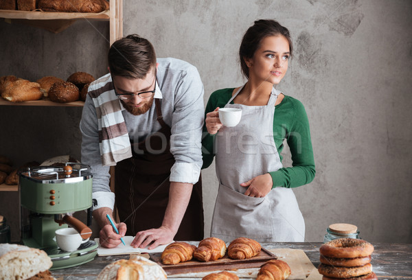 Yong man and woman trying to cook bread Stock photo © deandrobot