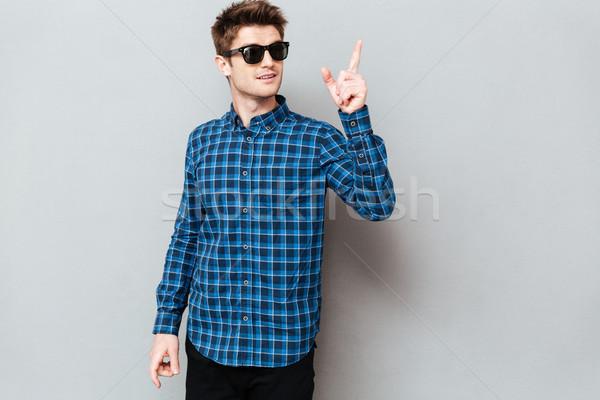 Homem bonito óculos de sol em pé cinza parede Foto stock © deandrobot