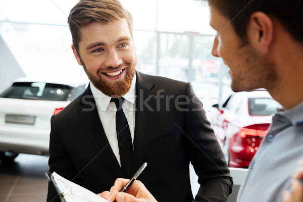 Smiling young dealer selling new car to a male customer Stock photo © deandrobot