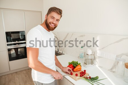 Side view of smiling bearded man cuts vegetables on kitchen Stock photo © deandrobot