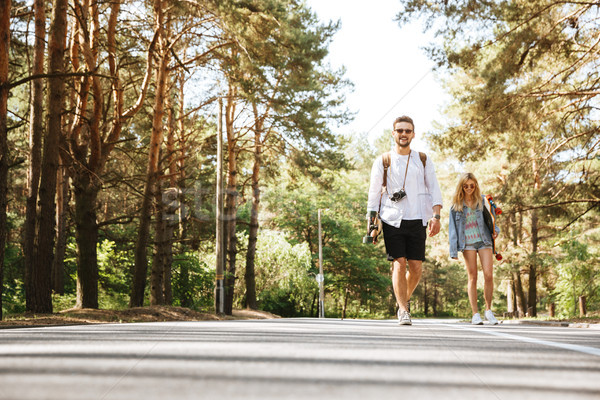 Loving couple walking with skateboards outdoors. Stock photo © deandrobot