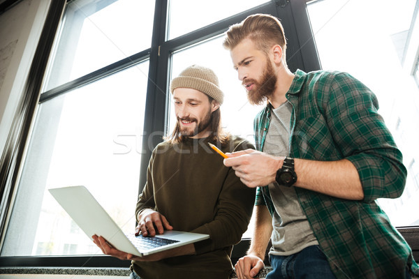 Young concentrated men colleagues in office using laptop Stock photo © deandrobot