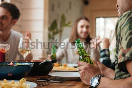 Happy young people clinking glasses and celebrating at the table Stock photo © deandrobot