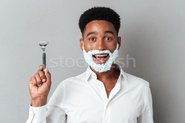 Happy cheerful african man with face in shaving foam Stock photo © deandrobot