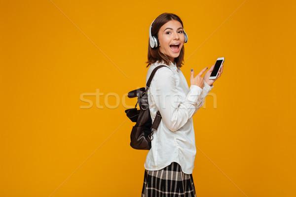 портрет возбужденный школьница равномерный наушники Сток-фото © deandrobot