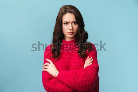 Portrait of upset freezing woman in red knitted sweater standing Stock photo © deandrobot