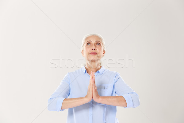 Beautiful old woman praying for peace, looking upward Stock photo © deandrobot