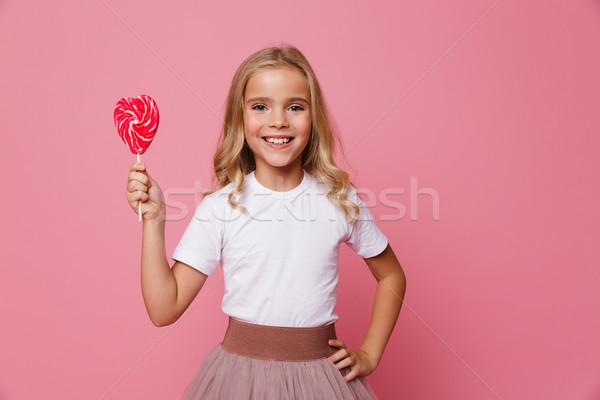 Stock photo: Portrait of a smiling little girl holding heart shaped lollipop
