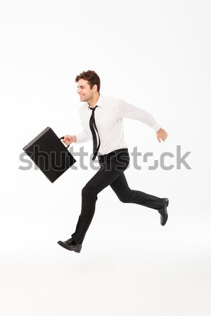 Full length portrait of a cheerful handsome businessman Stock photo © deandrobot