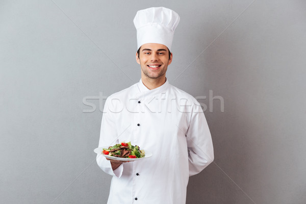 Happy young cook in uniform holding salad. Stock photo © deandrobot