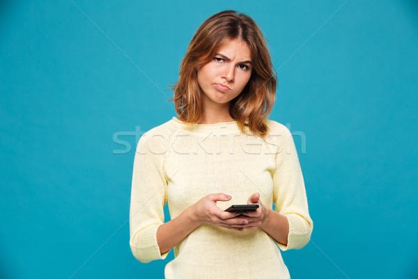 Elégedetlen nő pulóver tart okostelefon néz Stock fotó © deandrobot