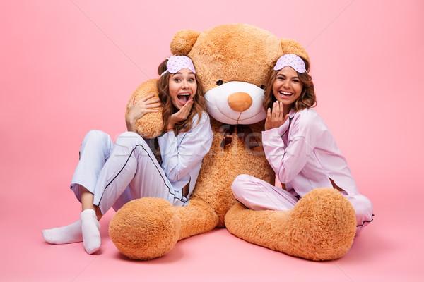 Kettő csinos derűs lányok pizsama ül Stock fotó © deandrobot