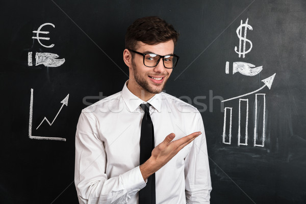 Young successful man in white shirt presenting new financial pro Stock photo © deandrobot