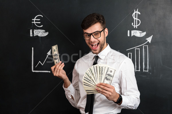 Happy young bearded man in glasses holding bunch of money, looki Stock photo © deandrobot