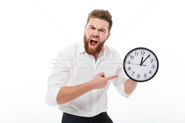 Screaming man in business clothes holding and pointing at clock Stock photo © deandrobot