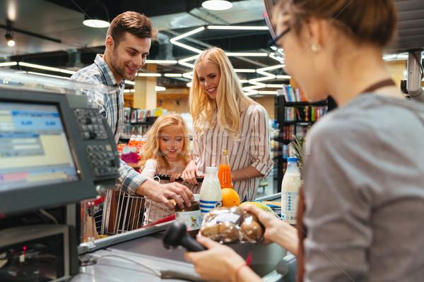 Fiatal család áll pénz pult vásárol Stock fotó © deandrobot