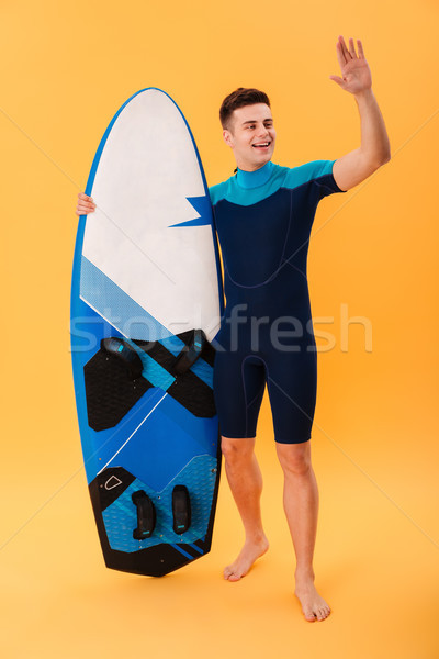 Full length photo of young surfer guy with surfboard showing gre Stock photo © deandrobot