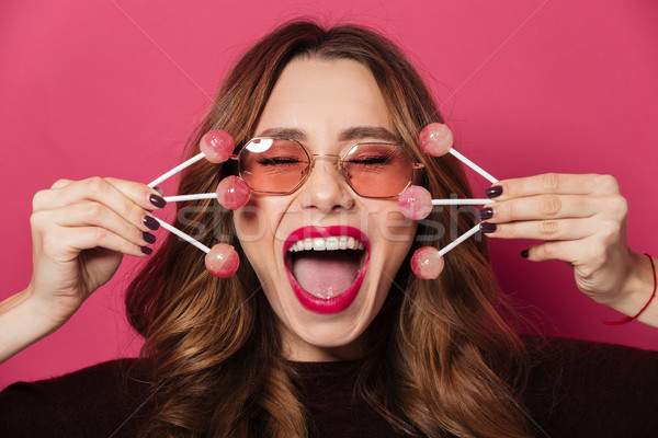 Excited screaming woman wearing glasses holding a lot of sweeties. Stock photo © deandrobot