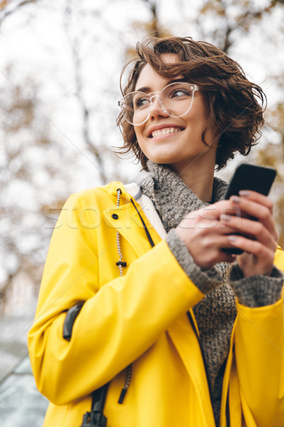 Smiling nice woman in yellow raincoat typing text message or scr Stock photo © deandrobot