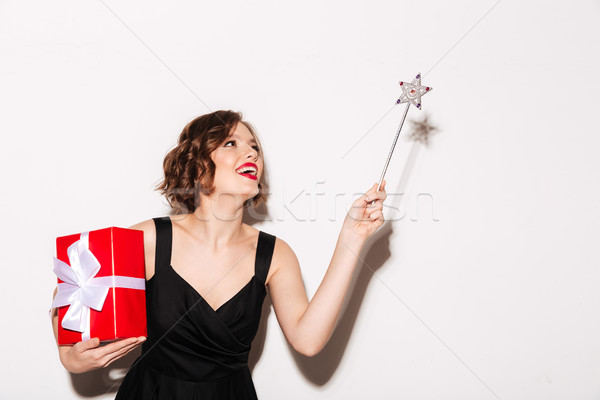 Portrait of a cheery girl dressed in black dress Stock photo © deandrobot