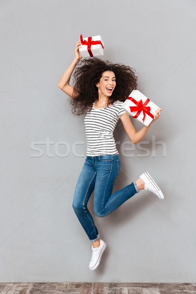 Happy emotions of positive woman in striped t-shirt and jeans en Stock photo © deandrobot
