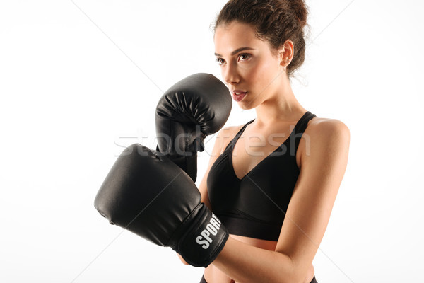 Serious curly brunette fitness woman in boxing gloves Stock photo © deandrobot