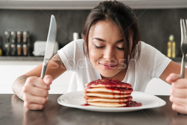 Hungry young woman sitting at the kitchen in home Stock photo © deandrobot