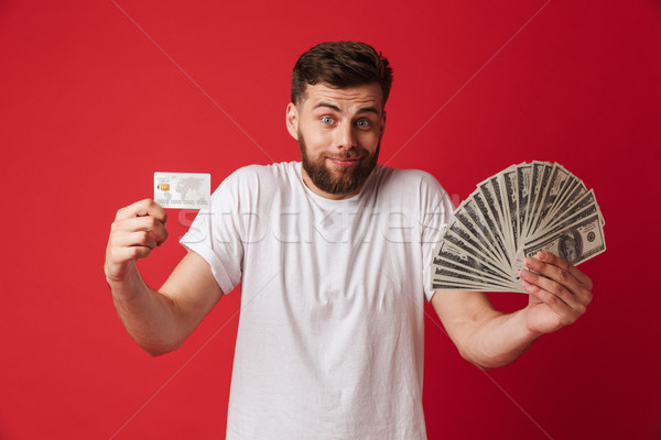 Confused young man holding money and credit card. Stock photo © deandrobot