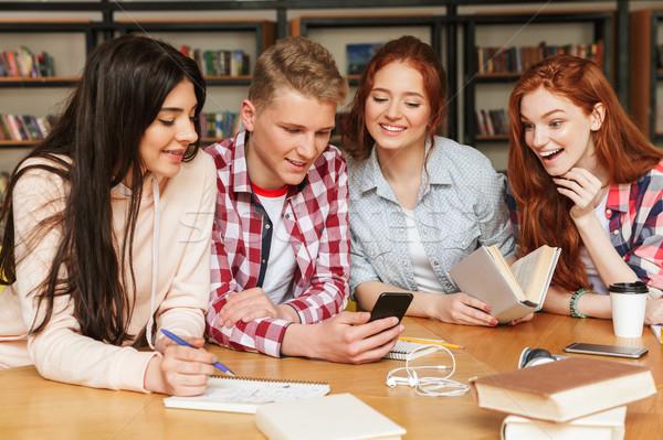 Groupe souriant adolescents devoirs séance bibliothèque Photo stock © deandrobot
