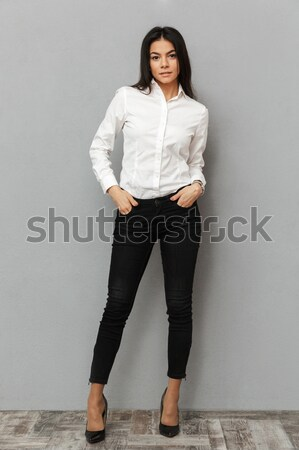 Full length image of stylish woman in formal wear smiling at cam Stock photo © deandrobot