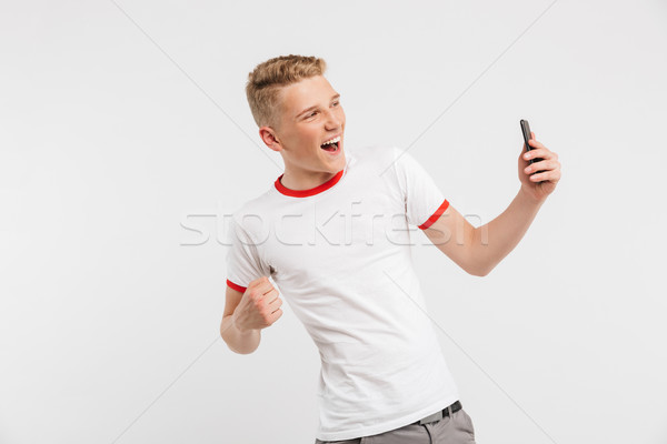 Photo of happy youngster wearing casual clothing screaming and c Stock photo © deandrobot