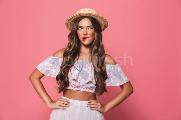 Portrait of seductive european woman 20s wearing straw hat bitin Stock photo © deandrobot