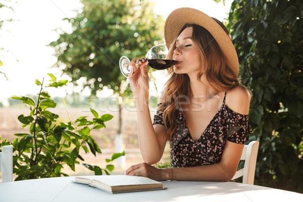 Photo of caucasian pretty woman wearing straw hat drinking wine, Stock photo © deandrobot