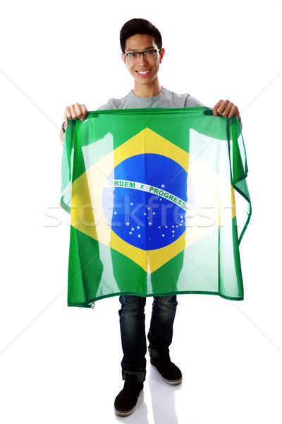 Portrait of a young asian man holding Brazilian flag over white background Stock photo © deandrobot