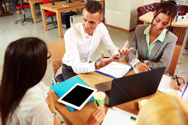 Happy business people having meeting around table in office Stock photo © deandrobot