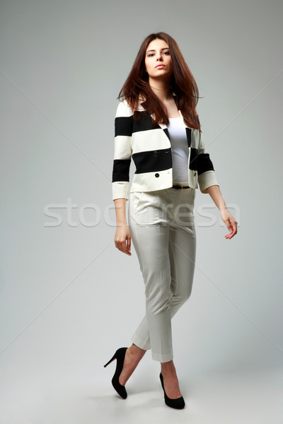 Full-length portrait of a young beautiful woman in casual clothes on gray background Stock photo © deandrobot