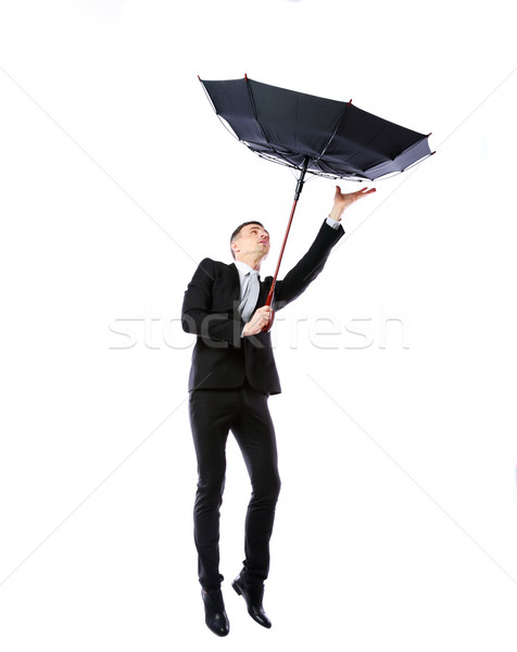 Businessman with umbrella fighting with strong wind over white background Stock photo © deandrobot