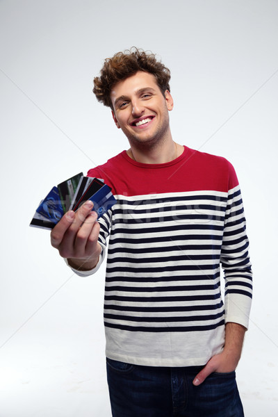 Happy young man holding credit cards over gray background Stock photo © deandrobot
