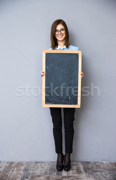 Happy businesswoman standing with billboard. Stock photo © deandrobot
