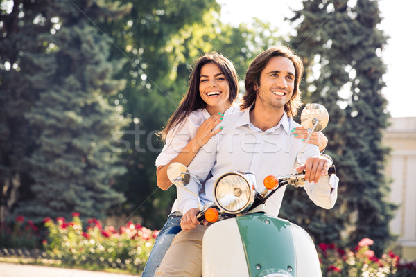 Cheerful young couple riding a scooter in town with fun Stock photo © deandrobot