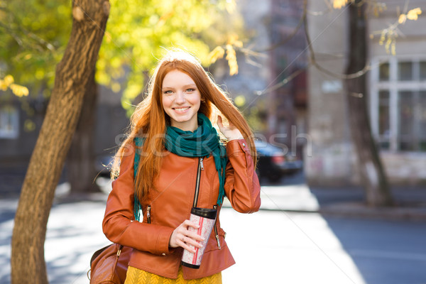 Smiling  positive woman holding tumbler of coffee  Stock photo © deandrobot