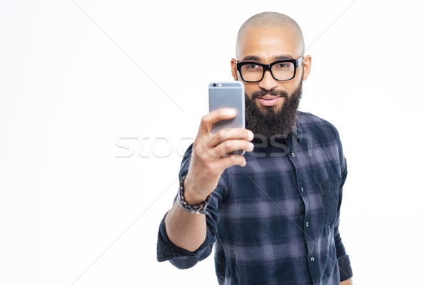Handsome african man with beard taking selfie using smartphone Stock photo © deandrobot