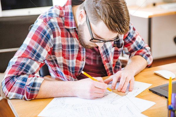 Serious hardworking student sitting at the desk and drawing blueprint Stock photo © deandrobot